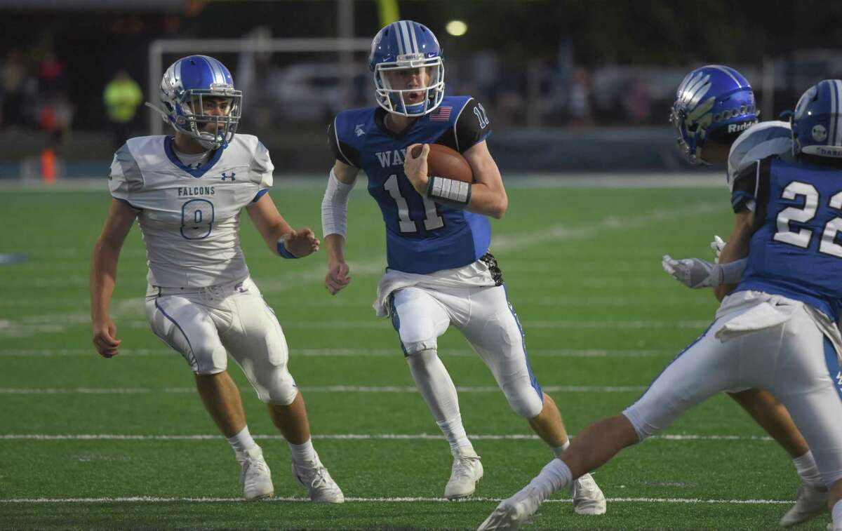 Darien quarterback Peter Graham (11) runs for a first down with Ludlowe's James Bourque (8) in pursuit during a football game at Darien High School on Sept. 13, 2019.