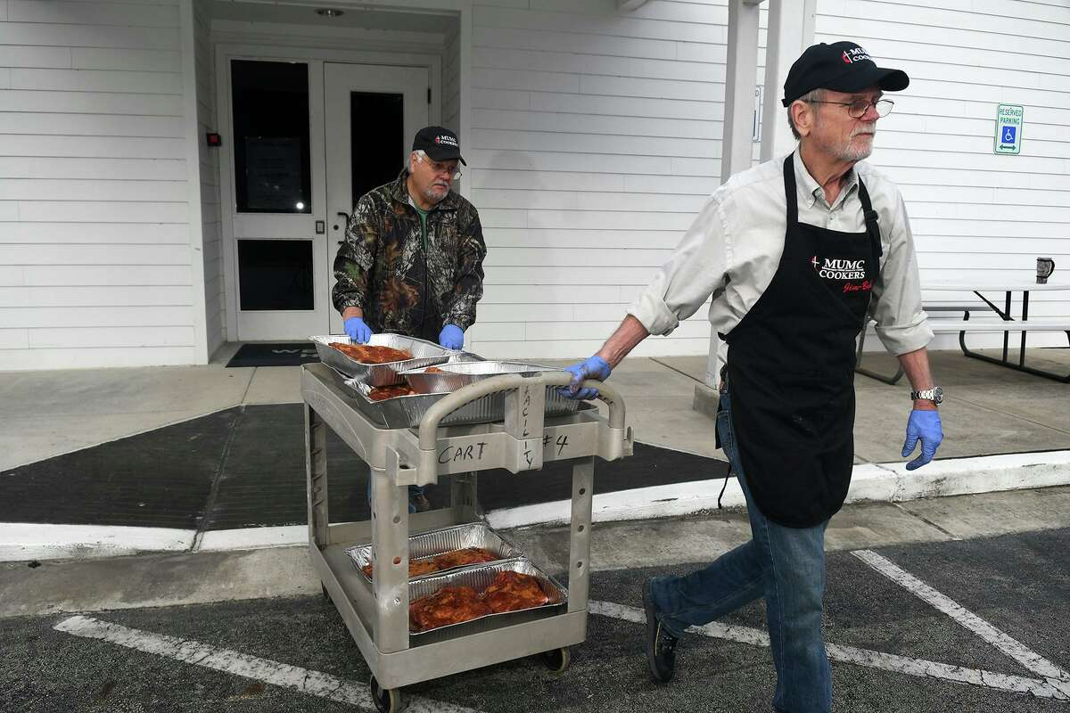 Montgomery United Methodist Church Cookers Jim Larson, right, and Mike Fulton transfer their pork butts from the kitchen to the pit during their