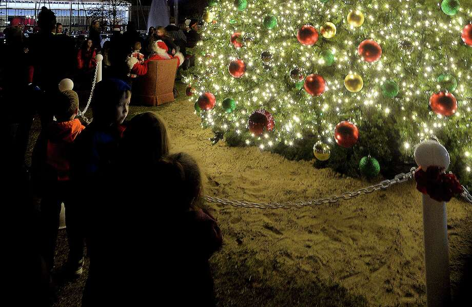 A crowd gathers round to take in the fireworks after the lighting of Beaumont's Christmas tree at the Event Centre Wednesday. The holiday festival featured this year's large tree, holiday activities, visits with Santa, and fireworks.  Photo taken Wednesday, December 5, 2018  Kim Brent/The Enterprise Photo: Kim Brent / Kim Brent/The Enterprise / BEN
