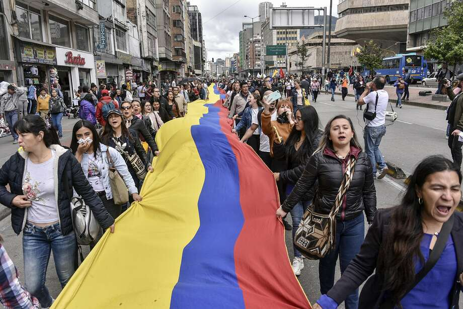 Anti-government demonstrators hold a giant Colombia flag during protests and a national strike against the government of conservative President Ivan Duque in the capital of Bogota. Photo: Guillermo Legaria / Getty Images