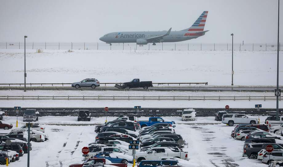 A jet passes cars parked at Denver's airport. Flights were delayed after a storm dropped nearly a foot of snow. Photo: Joe Mahoney / Getty Images