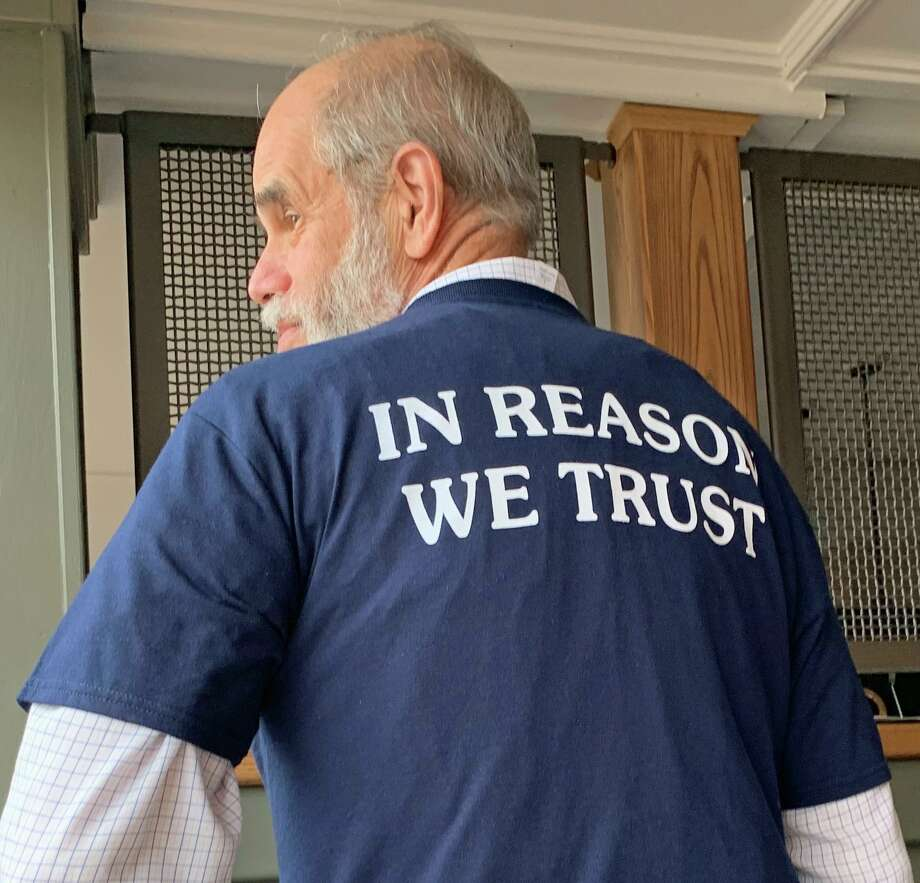 Cary Shaw shows the back of the new Humanists of Fairfield County shirt. Photo: Jacqueline Smith / Hearst Connecticut Media Group