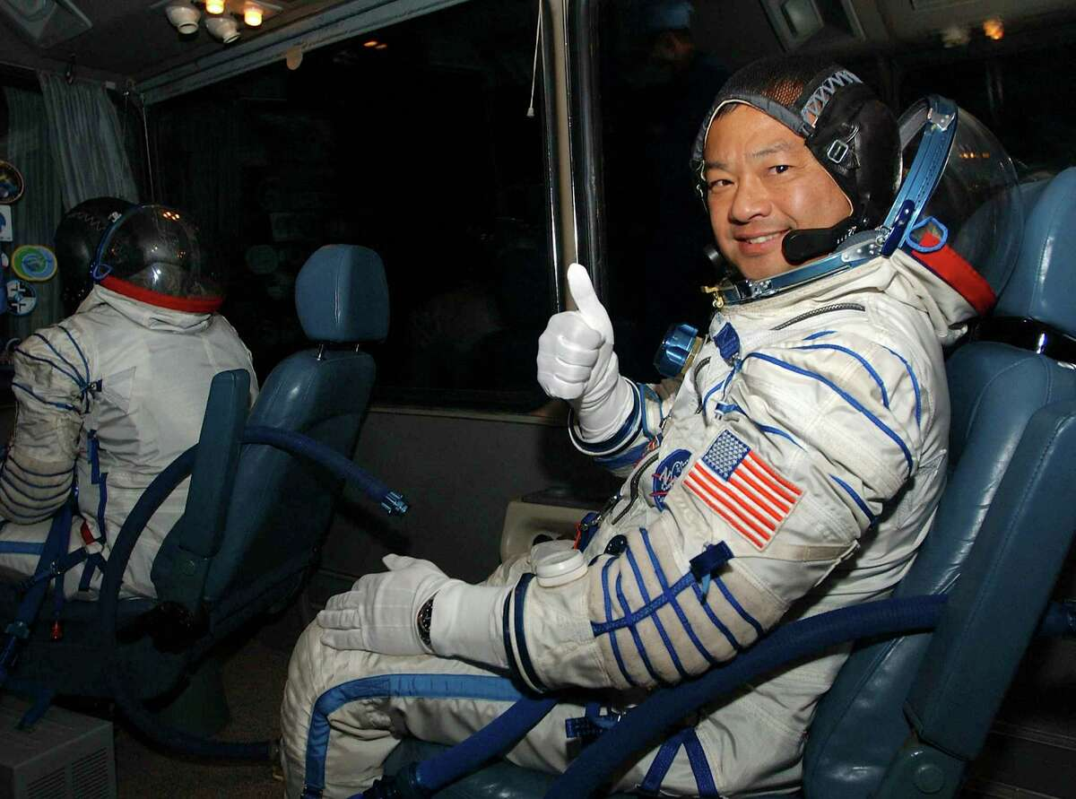American astronaut Leroy Chiao, right, gives a thumbs-up during the ride from the suit up facility at the Baikonur cosmodrome in Kazakhstan to the launch pad as he and his Soyuz TMA-5 spacecraft crewmates, Russian cosmonauts Salizhan Sharipov and Yuri Shargin, prepare for their liftoff Thursday, Oct. 14, 2004, to the international space station. The spaceship is due to dock with the station at 8:17 a.m. (0417 GMT) on Saturday. (AP Photo/NASA, Bill Ingalls)