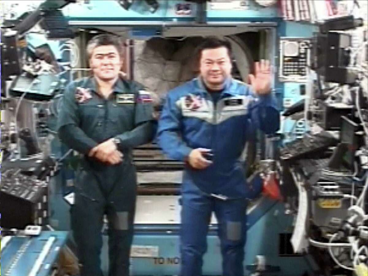 In this image from NASA television, International Space Station Expedition 10 Commander Leroy Chiao, right, waves at the start of a news conference as flight engineer Salizhan Sharipov stands by. During the end of the year news conference, the crew talked about the food supply aboard the ISS and the return of the Shuttle. (AP Photo/NASA TV)