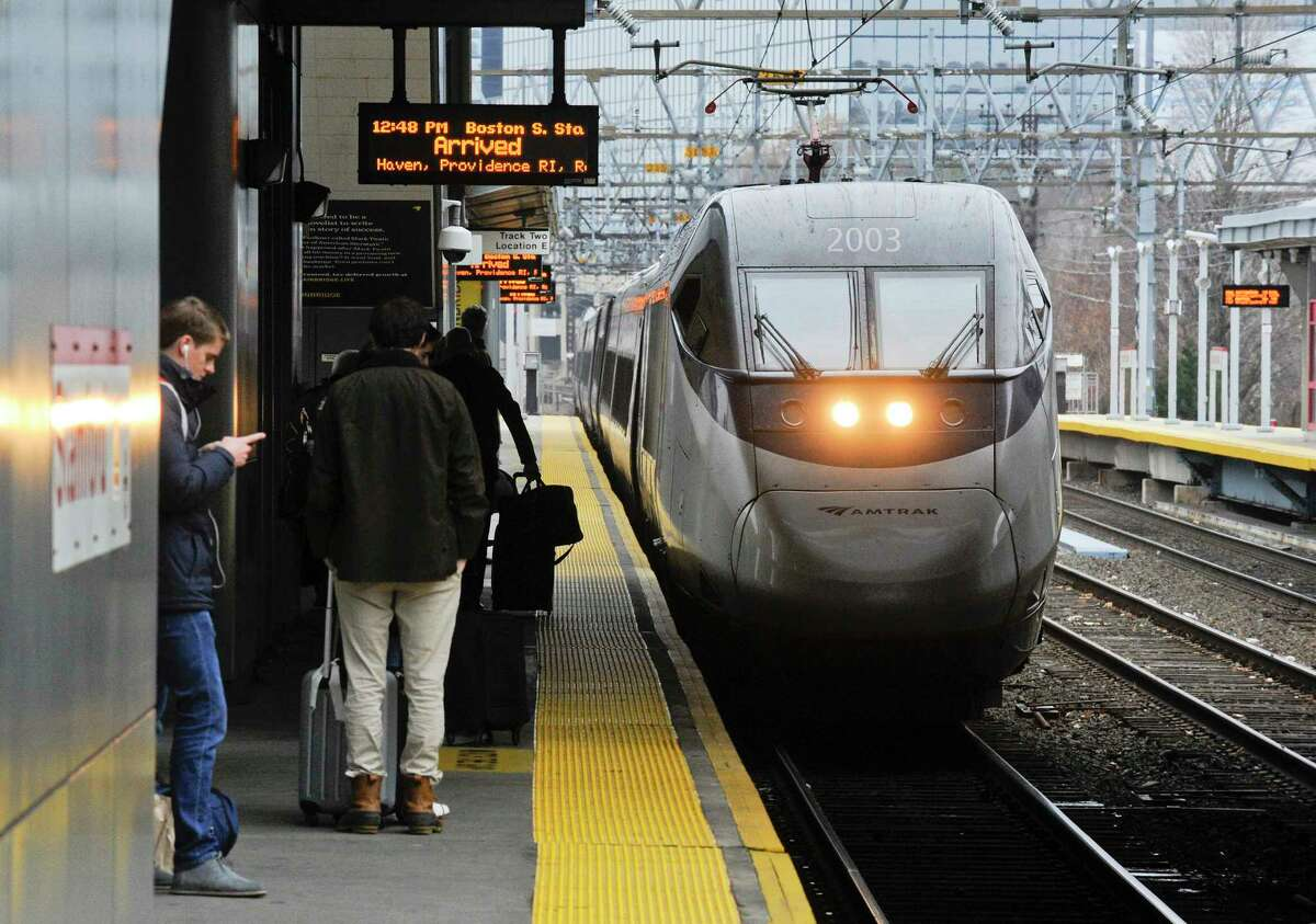 Passengers wait on the platform as the Amtrak Acela to Boston, Mass. arrives at the Stamford Train Station on Nov. 27, 2019.