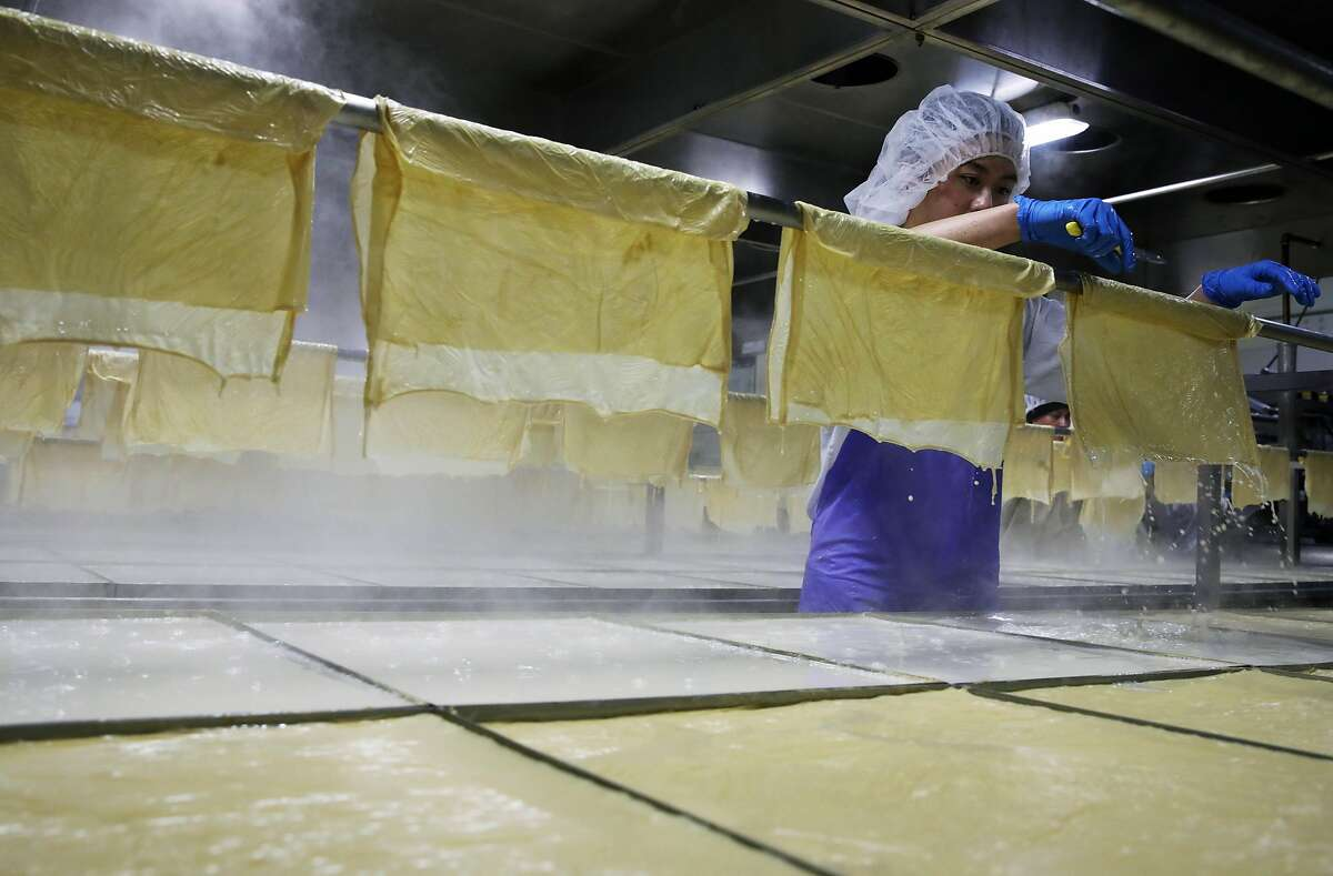 Savannah Zhong, an employee at Hodo Soy, hangs soy sheets in the facility in Oakland, Calif., on Tuesday, November 26, 2019. Many of its customers use the product to make a faux turkey for Thanksgiving.