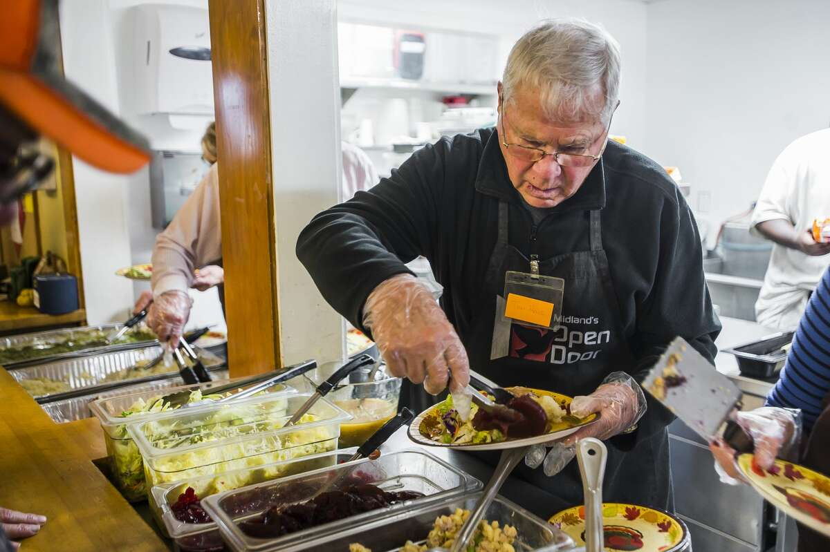 Volunteers serve dozens of people during a Thanksgiving meal Wednesday, Nov. 26, 2019 at Midland's Open Door. The organization will also serve an Italian-style feast at 6 p.m. on Thanksgiving, Thursday, Nov. 27, which is open to the public. (Katy Kildee/kkildee@mdn.net)