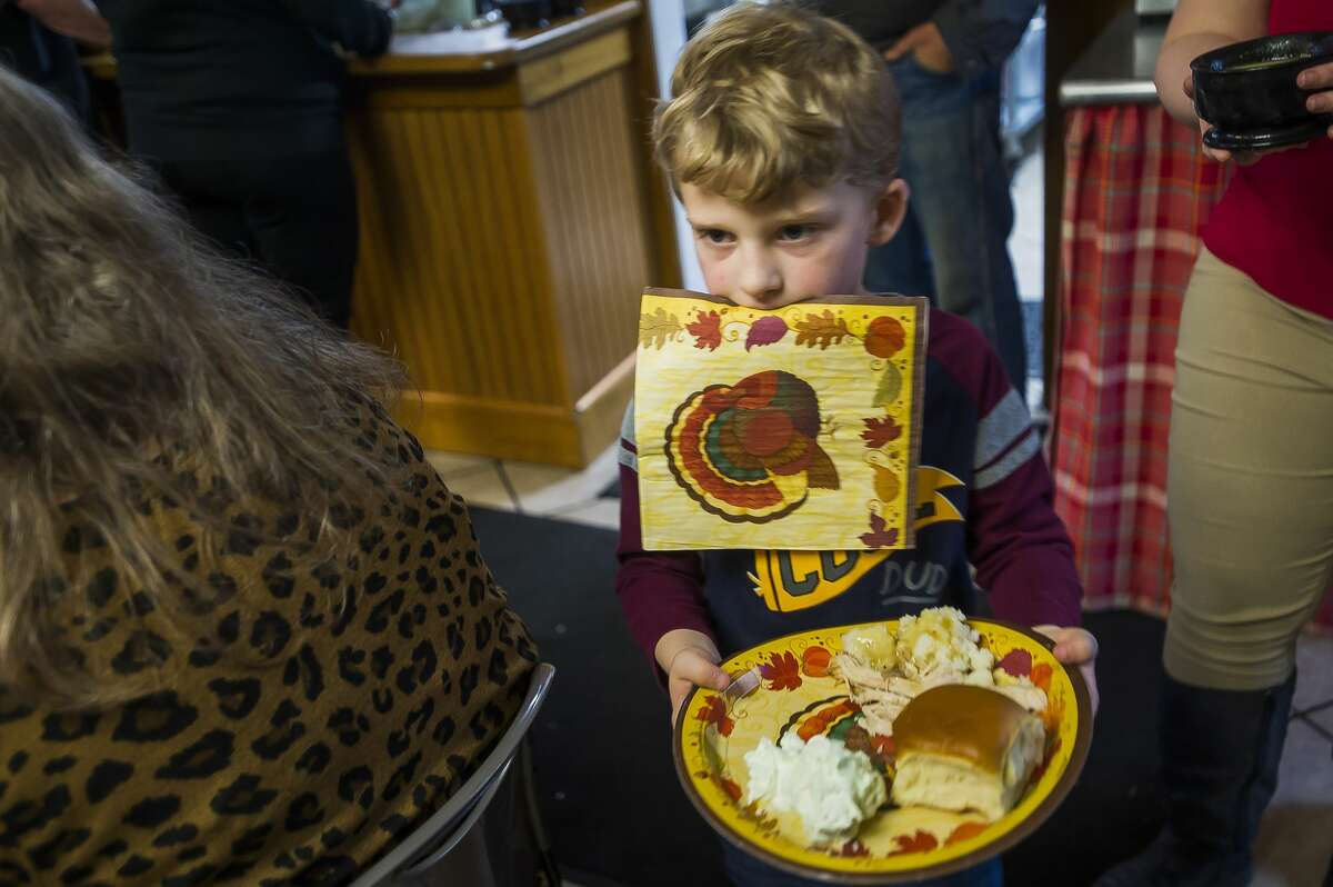 Caleb Burton, 7, carries a napkin in his mouth as he brings his food to his table during a Thanksgiving meal Wednesday, Nov. 26, 2019 at Midland's Open Door. The organization will also serve an Italian-style feast at 6 p.m. on Thanksgiving, Thursday, Nov. 27, which is open to the public. (Katy Kildee/kkildee@mdn.net)