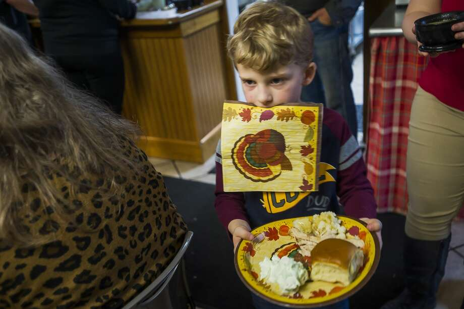 Caleb Burton, 7, carries a napkin in his mouth as he brings his food to his table during a Thanksgiving meal Wednesday, Nov. 26, 2019 at Midland's Open Door. The organization will also serve an Italian-style feast at 6 p.m. on Thanksgiving, Thursday, Nov. 27, which is open to the public. (Katy Kildee/kkildee@mdn.net) Photo: (Katy Kildee/kkildee@mdn.net)