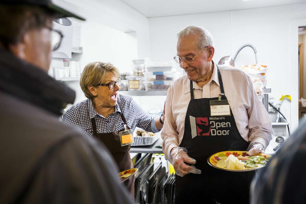 Judy Howe, left, laughs with fellow volunteer Bob Baker, right, as they serve guests during a Thanksgiving meal Wednesday, Nov. 26, 2019 at Midland's Open Door. The organization will also serve an Italian-style feast at 6 p.m. on Thanksgiving, Thursday, Nov. 27, which is open to the public. (Katy Kildee/kkildee@mdn.net)