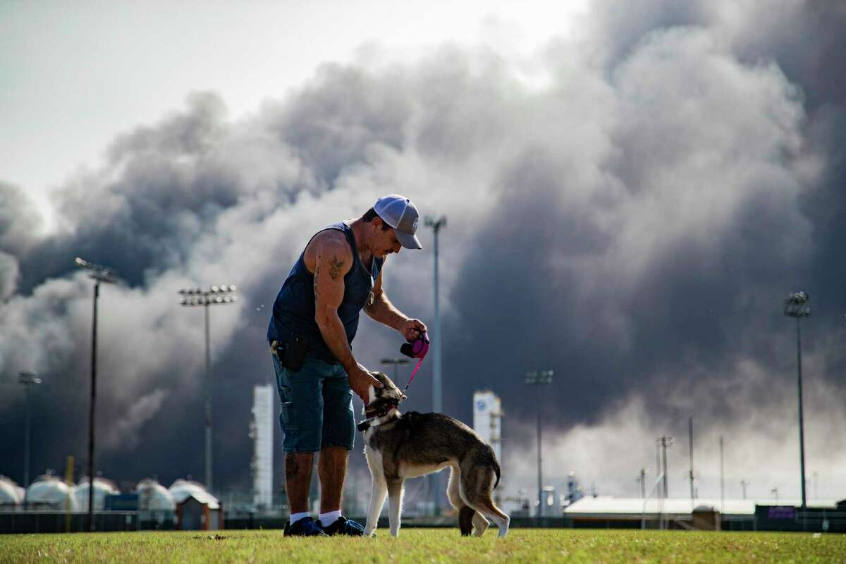 Ray Moore trains his dog Aries with a cloud of smoke on the background from the TPC Group Port Neches Operations explosion on Wednesday, Nov. 27, 2019, in Port Neches.