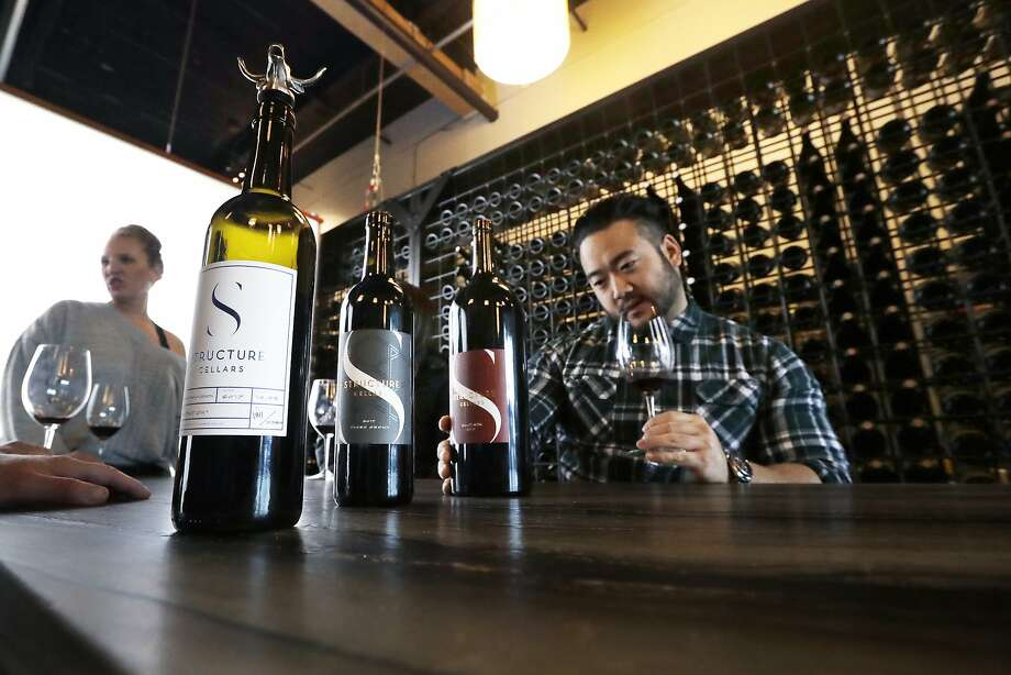 Mike Roh smells a wine sample before tasting it at the Structure Cellars tasting room in Seattle. Photo: Photos By Elaine Thompson / Associated Press