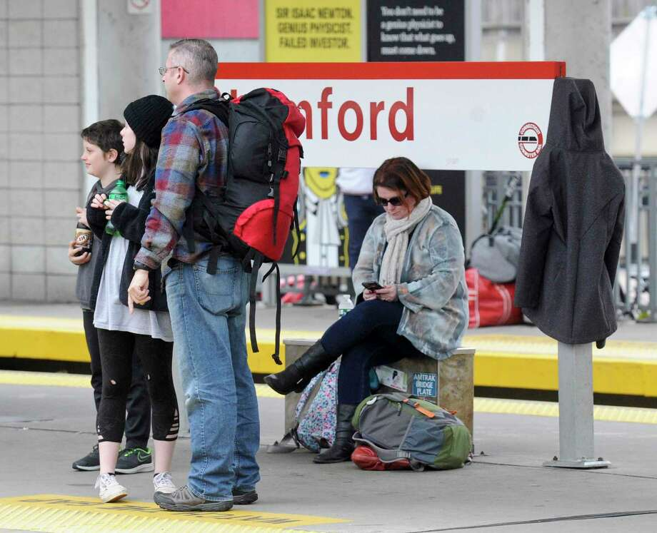 Bernadette Giandomenico checks her phone as she waits with her family, Husband Paul and children Danny, 10, his sister Maya, 11, to catch the Metro North Train to New York city at the Stamford Train Station on Nov. 27, 2019 in Stamford, Connecticut. The family is spending the holiday in New York City and taking in the Macy's Thanksgiving Parade. Photo: Matthew Brown / Hearst Connecticut Media / Stamford Advocate