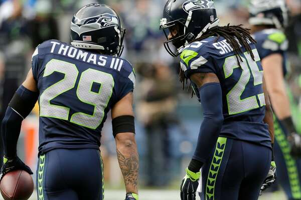 Seattle Seahawks' Earl Thomas, left, and Richard Sherman, right, talk the field before an NFL football game against the St. Louis Rams Sunday, Dec. 28, 2014, in Seattle. (AP Photo/John Froschauer)