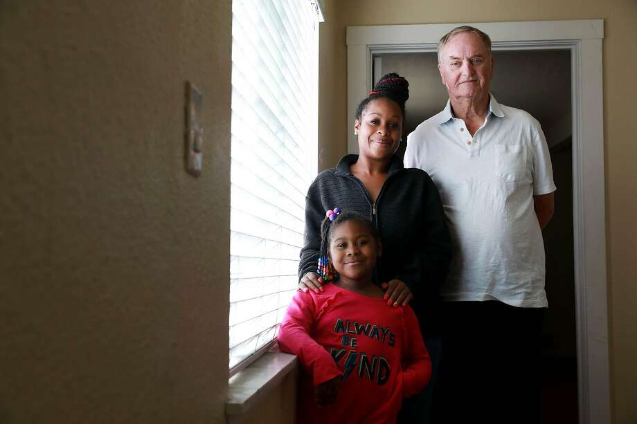 Tashawna Harris and her daughter, Angel, 5, inside their Oakland apartment with Robert Waggener. Photo: Yalonda M. James / The Chronicle