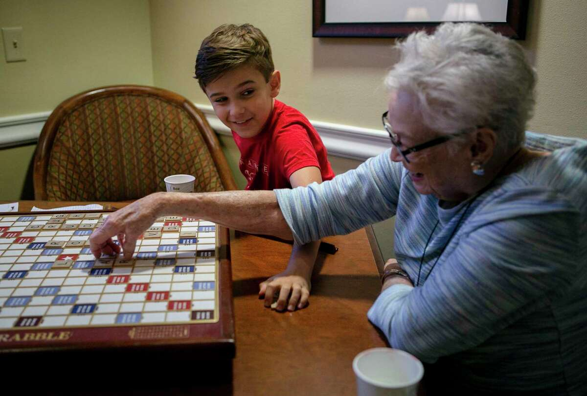 Ricky Rodriguez, 10, grins at Pat Griffith as they collect the tiles from their game at Brookdale Shavano Park in San Antonio on Nov. 24, 2019. Pat Griffith and Ricky play each other every Sunday to help Rocky practice. Ricky competed in the World Youth Scrabble Championship in Malaysia from Nov. 29 to Dec. 1.