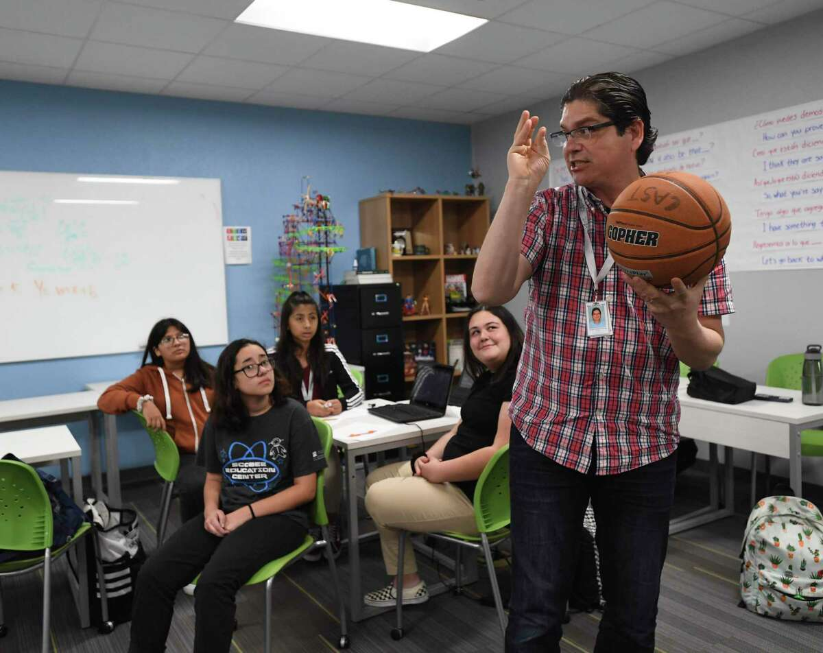 Oscar Garcia, a math teacher at CAST Med High School, uses a basketball to explain parabolic curves to students Daisy Hernandez, left, Kailey Nenque-Cazares, Celeste Rodriguez and Mikaley Kester on a recent Friday. The school offers a dual language program, as well as a curriculum that prepares students for careers in the medical field.