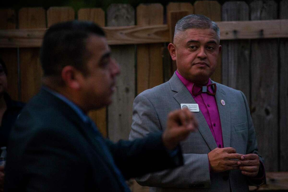 Eduardo Hernández, the Edgewood ISD superintendent, right, listens as the school district's Police Chief Jesse Quiroga speaks during a platica, a neighborhood conversation at a resident's home, on Oct. 28.