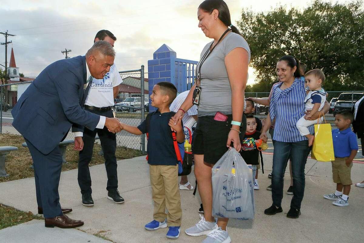 Edgewood ISD Superintendent Eduardo Hernandez, left, greets kindergartner Emanuel Ruiz, 5, and his mother, Mercy Ruiz, on the first day of school at Gardendale Elementary School in 2019.