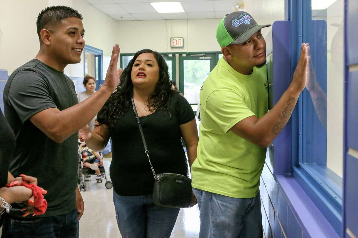 Lorenzo Rodriguez, from right, Sabrina Ruiz and Alex Ruiz look through a window into a classroom at Gardendale Elementary School on the first day of school last August. Edgewood ISD has partnered with the city's Pre-K 4 SA to turn the school into an early education center. Other school districts also are expanding preschool offerings. Eligibility to most public programs is based on household income, leaving access for middle class families a continuing problem.