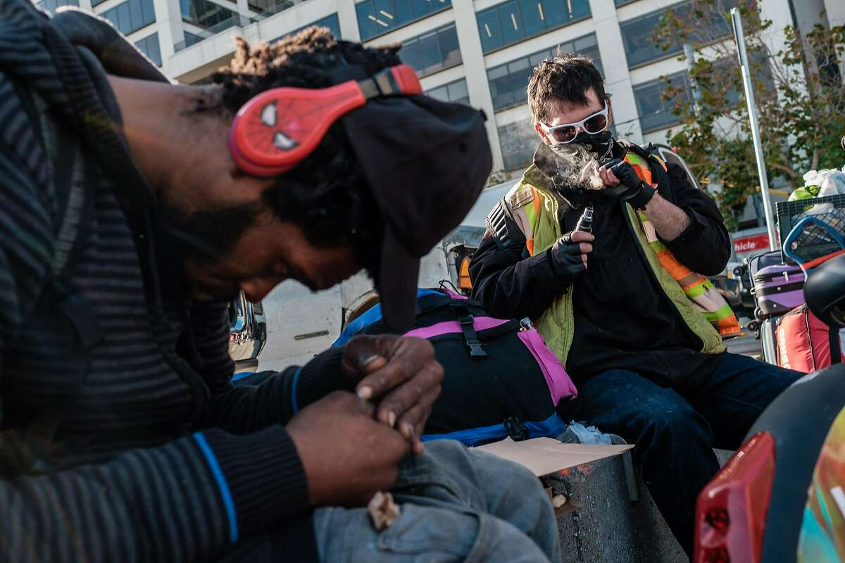 A man who goes by the name Country, right, smokes meth on the plaza near the Embarcadero in San Francisco, Calif. on Thursday, November 21, 2019.