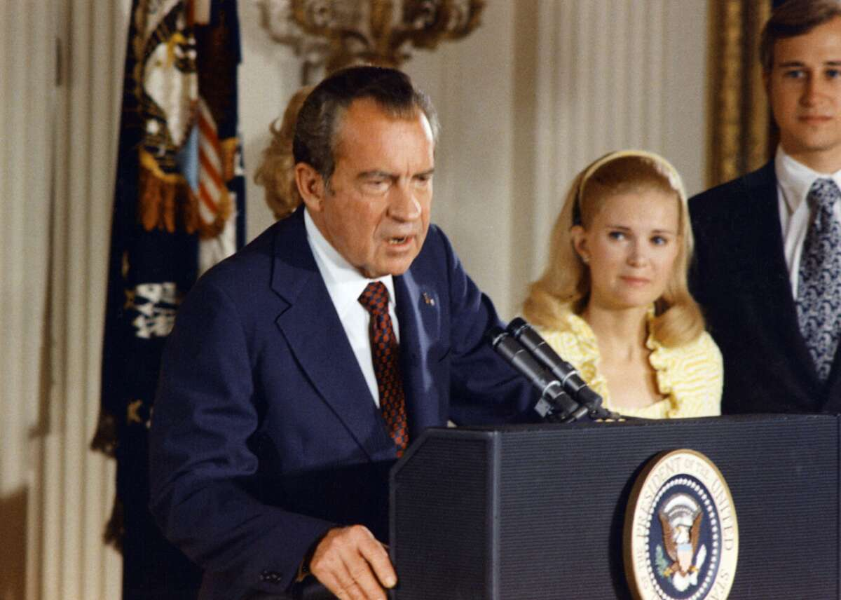 The 37th president of the United States, Richard Nixon, bids farewell to the White House staff on August 9. Family members are (L-R): First Lady Pat Nixon, hidden behind the president, daughter Tricia Nixon Cox, and her husband Edward Cox.