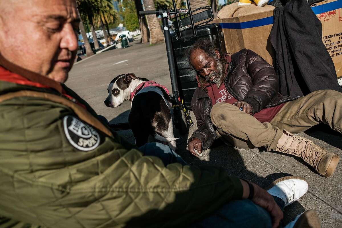 Stevon Williams, right, and David Valenzuela sit on the plaza near the Embarcadero in San Francisco, Calif. on Thursday, November 21, 2019.