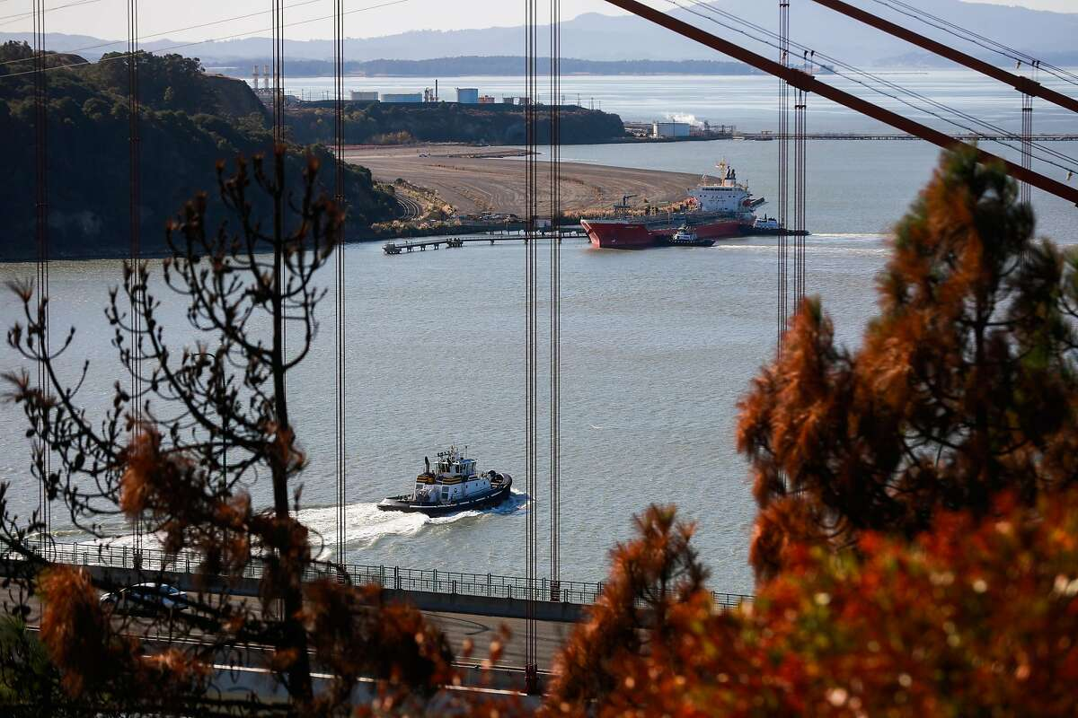 A tugboat passes through the Carquinez strait while a chemical tanker is seen docked on Monday, November 25, 2019, in Vallejo, California.