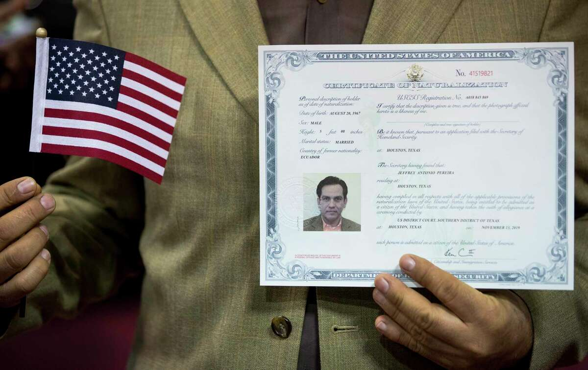 Jeffrey Antonio Pereira, a native of Equador, shows off his certificate of naturalization following a naturalization ceremony for more than 2,500 new citizens at the M.O. Campbell Educational Center on Wednesday, Nov. 13, 2019, in Houston. As the state gears up for what could be its most important election in decades, thousands of would-be voters are caught in limbo, stuck in a deep and growing backlog of immigrants applying for U.S. citizenship. While the Trump administration says it is devoting resources to cut down on the backlog, and attorneys in Houston say immigrations officials do appear to be making an effort to get more applications through.