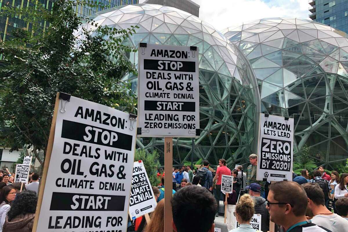 FILE - In this Friday, Sept. 20, 2019 file photo, Amazon workers begin to gather in front of the Spheres, participating in the climate strike in Seattle. Employee activism and outside pressure have pushed big tech companies like Amazon, Microsoft and Google promising to slash their carbon emissions. Microsoft and other tech giants have been competing to strike lucrative partnerships with ExxonMobil, Chevron, Shell, BP and other energy firms. (AP Photo/Elaine Thompson, File)