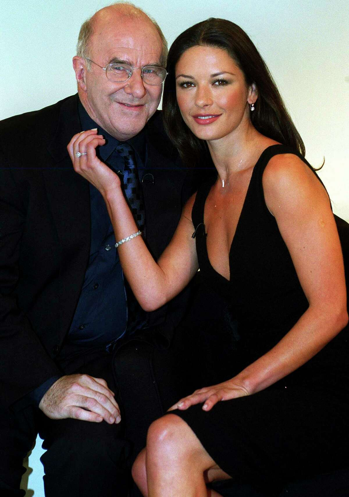 FILE - In this June 27 1999 file photo, actress Catherine Zeta-Jones poses for a photo with broadcaster Clive James for