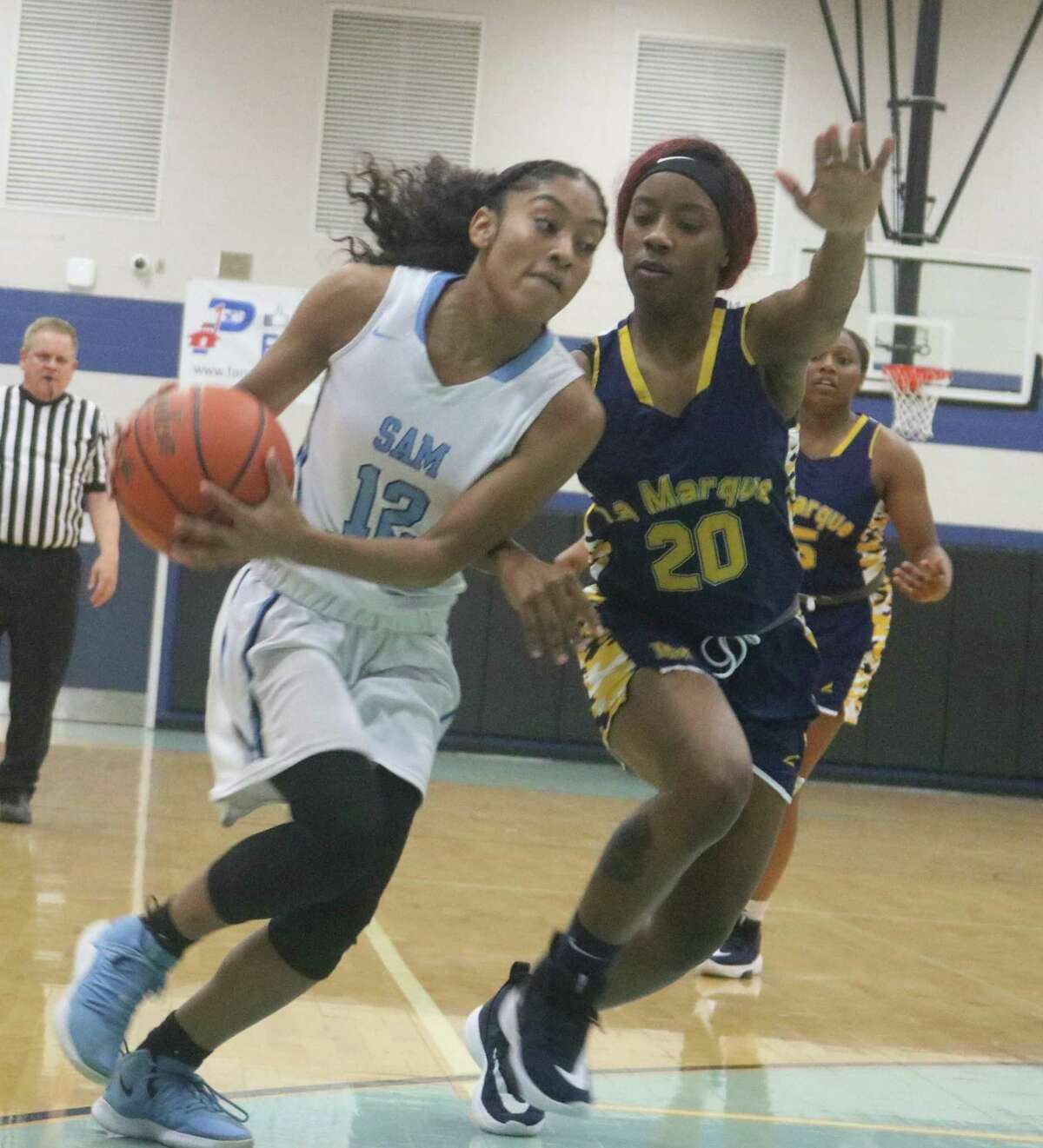 Despite a Lady Cougar on her shoulder, Sam Rayburn's Sally Patricio heads for two of her 10 points she scored in the third period against La Marque. Patricio finished with a game-high 17 points.
