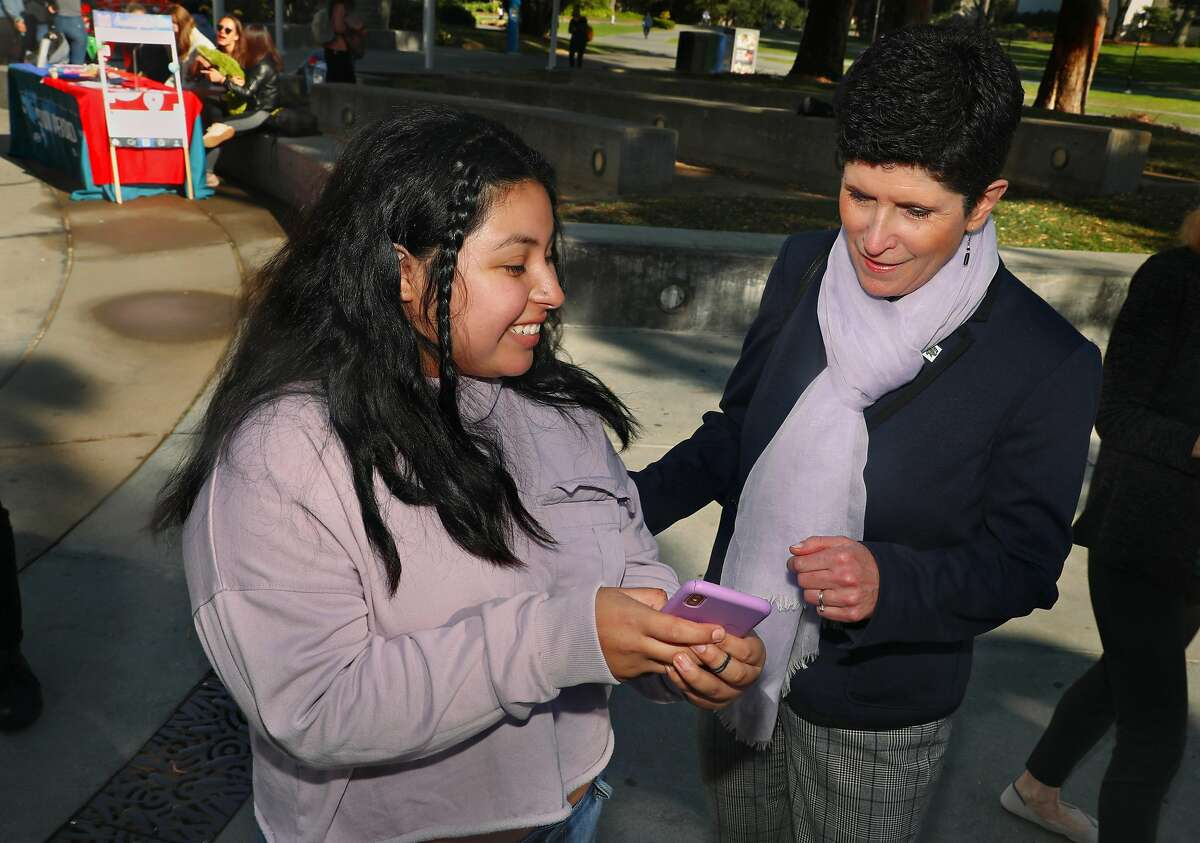 Student Diana Velazquez (left) shows new San Francisco State University president Lynn Mahoney (right) phone pictures of a past weekend day in Berkley during Walk for Breast Cancer awareness on Monday, Nov. 4, 2019, in San Francisco, Calif.