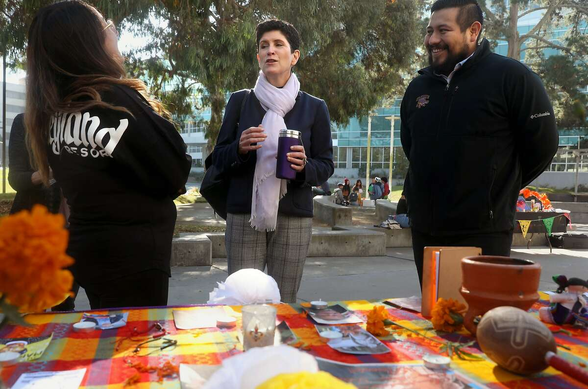 New San Francisco State University president Lynn Mahoney (middle) chats with students including Leslie Jackson (left), fourth year business marketting major, at a table commemorating Dia de los Muertos in front of the student union on Monday, Nov. 4, 2019, in San Francisco, Calif. At right is administrative support Luis De Paz Fernandez.