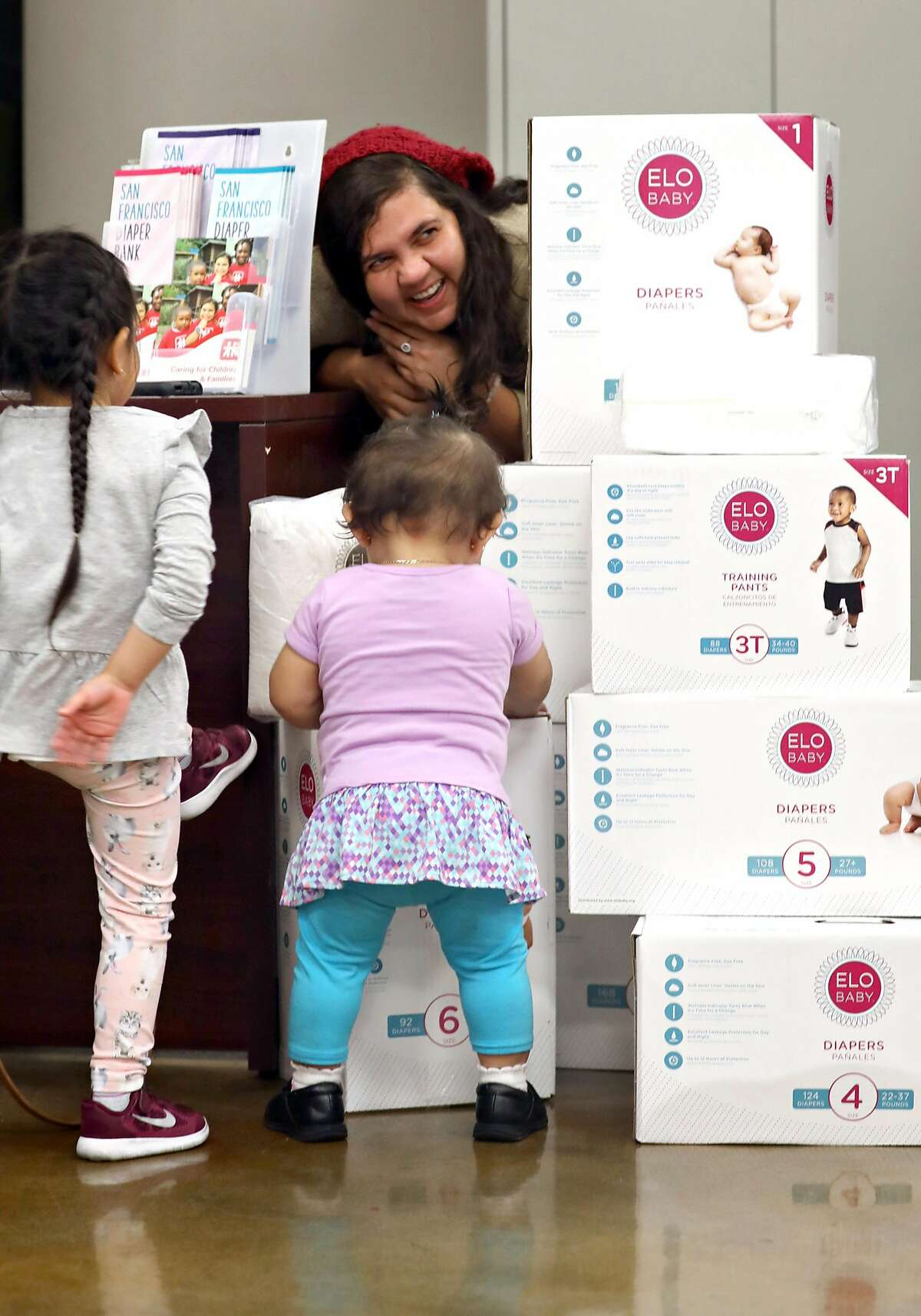 Resource and referral services Marcela Araujo (middle) at the diaper bank where Camila Saavedra-Montano (left), 3 years old, and Jimena Sarci Rivas (middle) browse her desk on Friday, Nov. 22, 2019, in San Francisco, Calif. San Francisco this month became the first county in the US to hand out free diapers with its SNAP (food stamp) benefits.