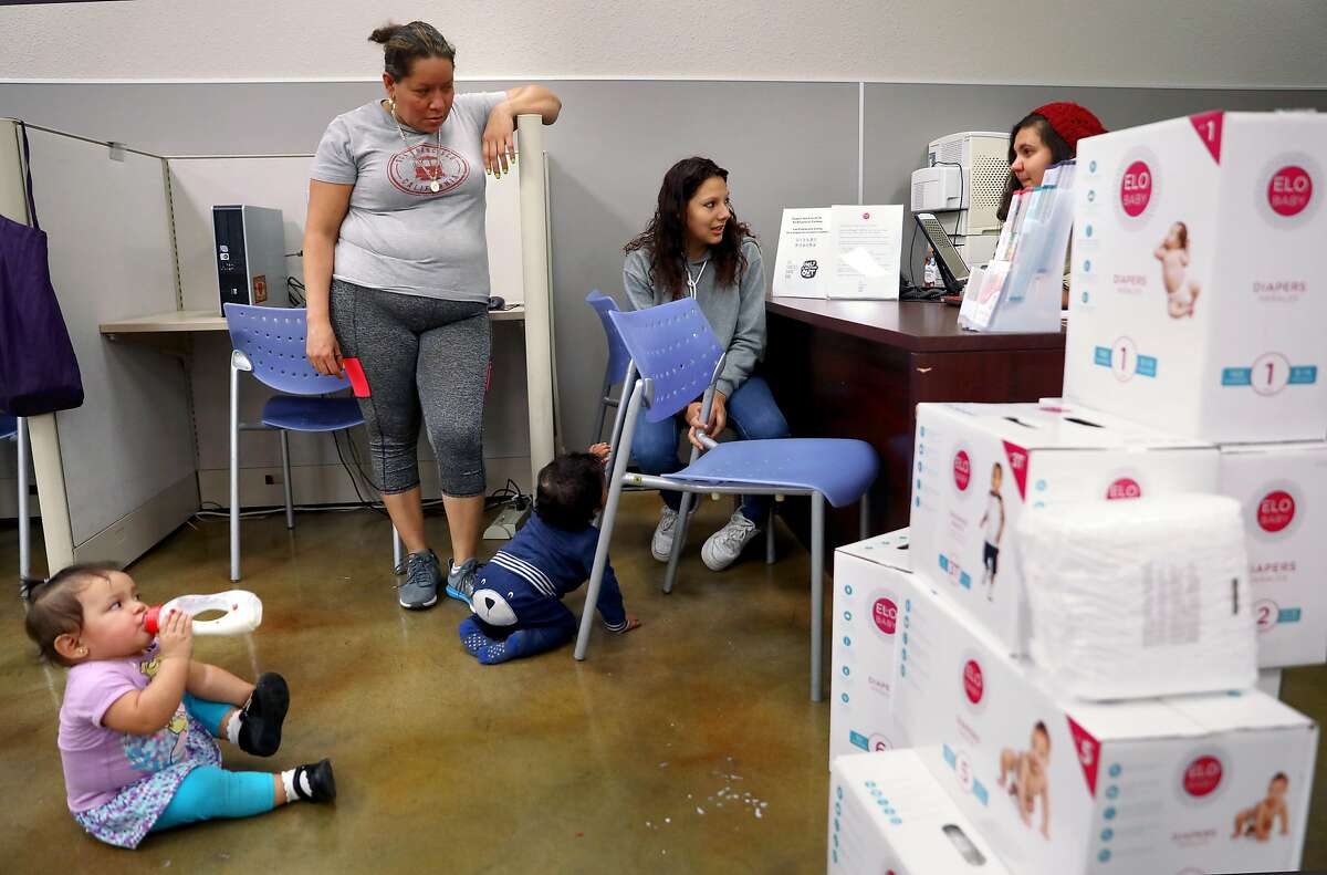 Lupita Mendoza (middle left)) with her one year old Jimena Sarci Rivas (front left) as Monse Delgado (middle) picks up diapers for her one year old Joe Yohander at the child care resource desk of the SF Human Services Agency on Friday, Nov. 22, 2019, in San Francisco, Calif. San Francisco this month became the first county in the US to hand out free diapers with its SNAP (food stamp) benefits.
