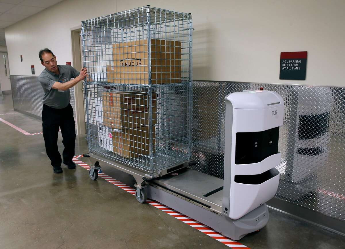 Kevin Hinoki loads a cart onto a Tug autonomous mobile robot which will deliver the supplies on its own at the Stanford Medical Center in Stanford, Calif. on Tuesday, Nov. 26, 2019. Twenty-three autonomous mobile robots will be joining a fleet of five already in service to deliver supplies and linen throughout the sprawling hospital.