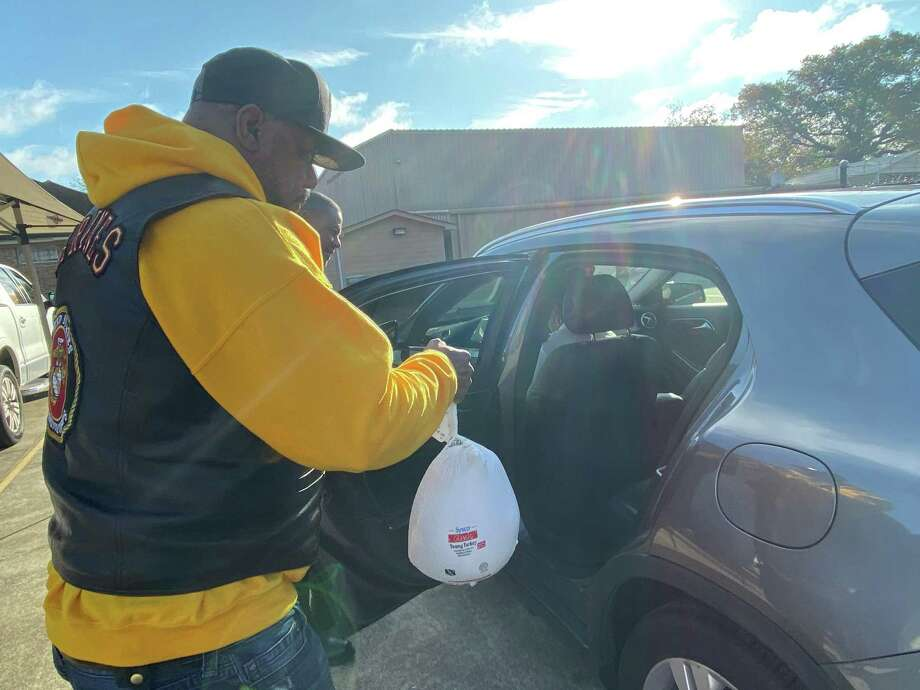 Dextel Word loads a turkey into the back of a car during a giveaway hosted by the Beaumont Hard Riders motorcycle club Saturday. Photo: Chris Moore