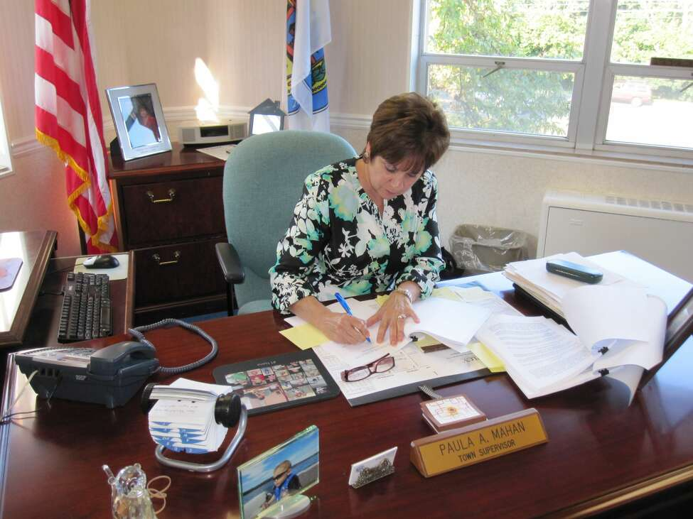 Paula Mahan sits at her desk in town hall in Colonie.