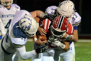 Newtown's James Knox (99), left, and teammate Jared Dunn (33) tackle Masuk QB Nicholas Saccu during football action in Monroe, Conn., on Wednesday Nov. 27, 2019.