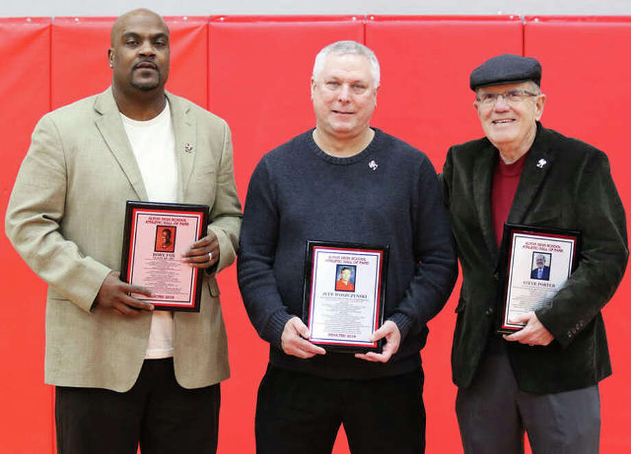 Alton High athletics recognized its 2019 Hall of Fame class at halftime of the Redbirds' boys basketball victory over St. Louis Carnahan in the Redbirds' Tip-Off Tournament at Alton High on Wednesday night. Inductees (from left) 1997 graduate and three-sport athlete Rory Fox (football, basketball and baseball), former boys and girls bowling coach Jeff Woszczynski and retired Telegraph sports writer Steve Porter (1973-2013) pose with their Hall of Fame plaques. The 1935 Redbirds football team that went 9-0 was also welcomed into the AHS Hall. Photo: Greg Shashack / The Telegraph