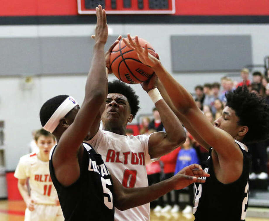 Alton's Moory Woods (0) powers up to score between Carnahan's Chris Rogers (left) and Raymond Emerson in the first half Wednesday night in the Redbirds' season-opening victory at the Alton Tournament. Photo: Greg Shashack / The Telegraph