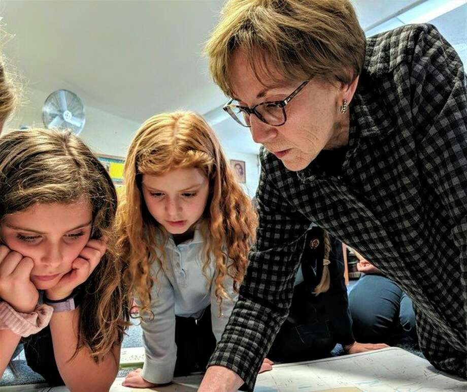 From left, Blessed Sacrament students Brynn Haddad and Lindsay Hofmeister watch attentively as Midland Mayor Maureen Donker, points out the different wards on a map of the city. (Photo provided)