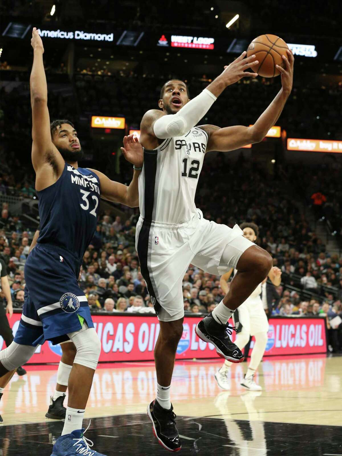 Spurs' LaMarcus Aldridge (12) drives toward the basket against Minnesota Timberwolves' Karl-Anthony Towns (32) during their game at the AT&T Center on Wednesday, Nov. 27, 2019.