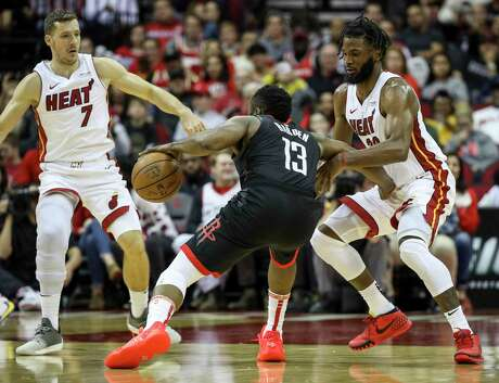 Heat forward Justise Winslow, right, and guard Goran Dragic (7) apply some tandem to defense to Rockets guard James Harden during a Nov. 27 matchup at Toyota Center.