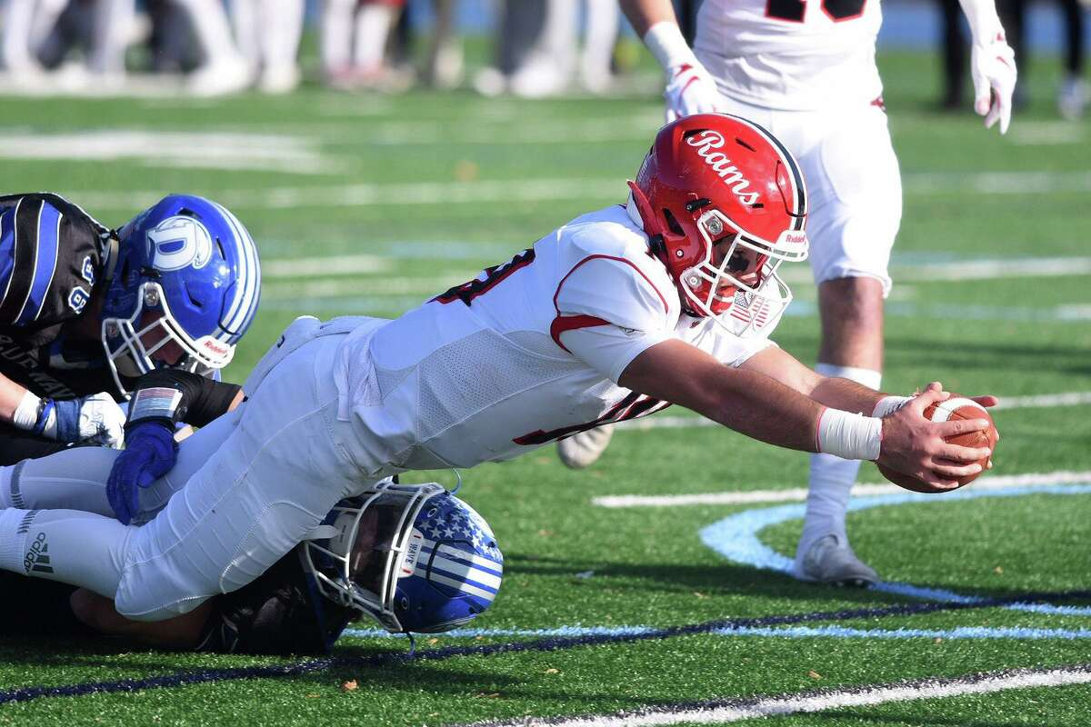 New Canaan quarterback Drew Pyne (10) stretches for a touchdown during the Rams' annual Turkey Bowl football game against Darien at Darien High School on Thursday. New Canaan won 20-0 for its third straight win in the series.