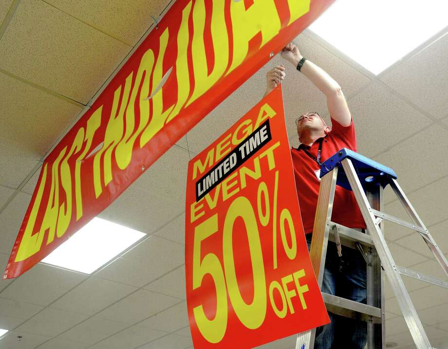 Parkdale Mall Stage store manager Jerrid Carpenter hangs signage advertising its final holiday sale Tuesday as they prepare for their pre-Black Friday doorbuster opening later that night. The Houston-based retailer is transitioning its stores to the Gordmans brand, which is planning to open in the spring of 2020. Photo taken Tuesday, November 26, 2019 Kim Brent/The Enterprise Photo: Kim Brent / The Enterprise / BEN