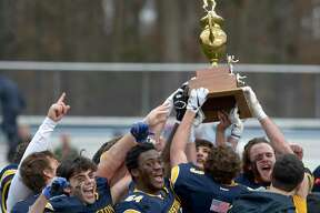 Weston seniors hold the trophy after winning the Thanksgiving football game between Joel Barlow and Weston high schools. Thursday, November 28, 2019, at Weston High School, Weston, Conn.