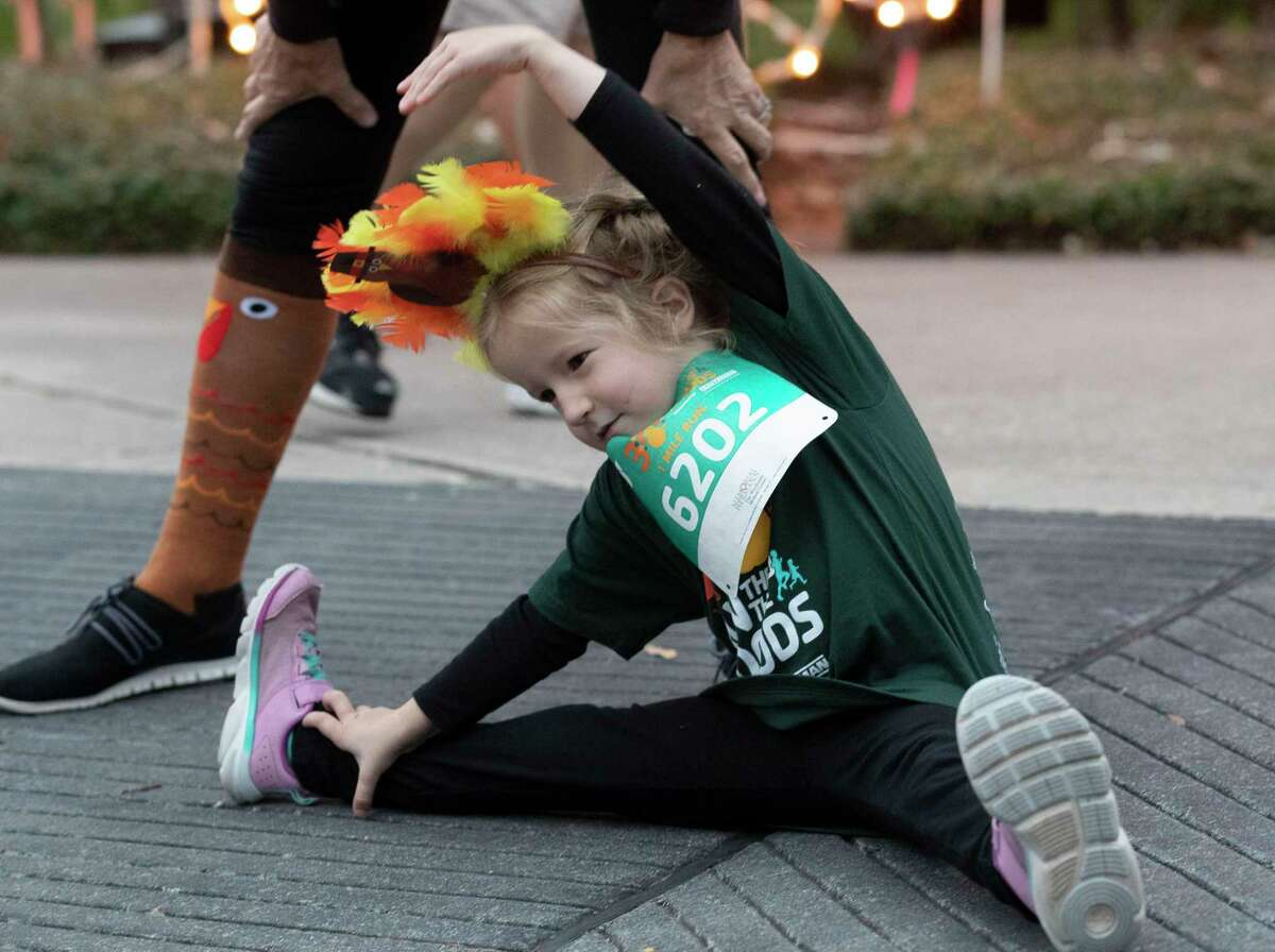 Lily Oliver stretches before taking part in the annual Run Thru the Woods, Thursday, Nov. 28, 2019, in The Woodlands. More than 5,200 runners took part in the annual run through The Woodlands on Thanksgiving Day.