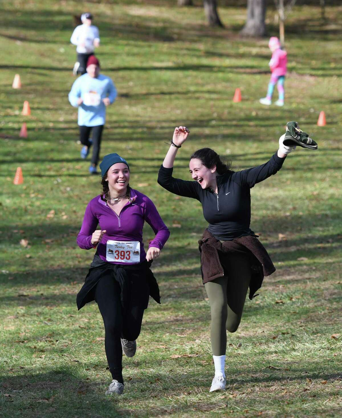 Stamford's Sophie Pigott, left, 16, and Norwalk's Cayla Bernstein, 16, celebrate as they cross the finish line at the 2019 Dental Oral Surgery Turkey Trot Beachfront Bushwhack at Greenwich Point Park in Old Greenwich, Conn. Thursday, Nov. 28, 2019. Presented by Dental Oral Surgery and Threads & Treads, 500 runners competed in the five mile cross-country race and kid's one mile fun run.